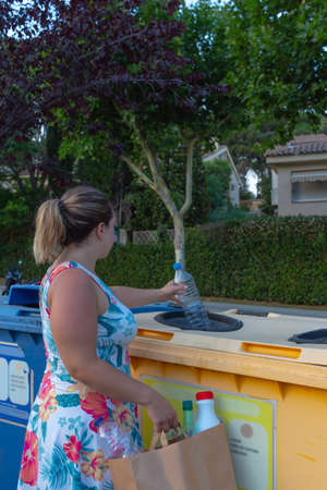 Girl recycling a plastic bottle, in a yellow dumpster, holding a paper bag full of plastic