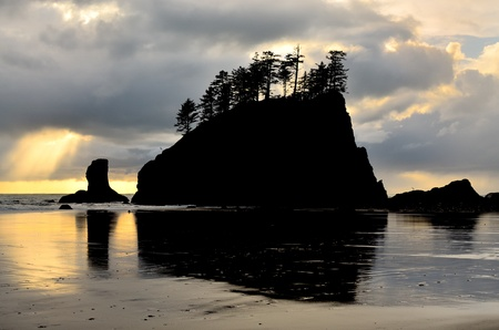 Silhouette of Sea Stack at Second Beach. A shaft of light breaks through the clouds.