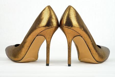 Paar gouden gekleurde hoge hak schoenen tegen een witte achtergrond