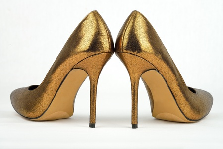Pair of golden colored High Heel shoes against white background Stock Photo