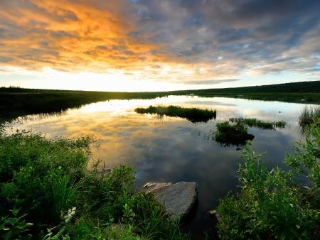 明るい雲にアラスカで黄金の夕日