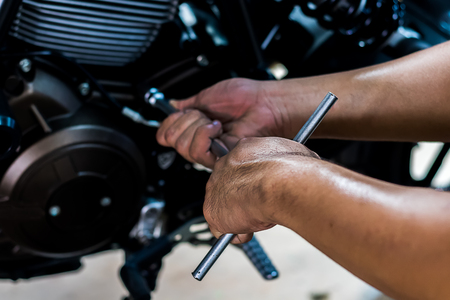 Image is close up. People holding hand are repairing a motorcycle Use a wrench and a screwdriver to work. Use the wrench to tighten the cylinder. Standard-Bild