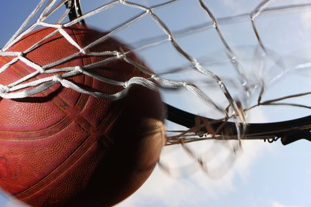 basketball hoop: Picture of a basketball field goal with the sky in background.