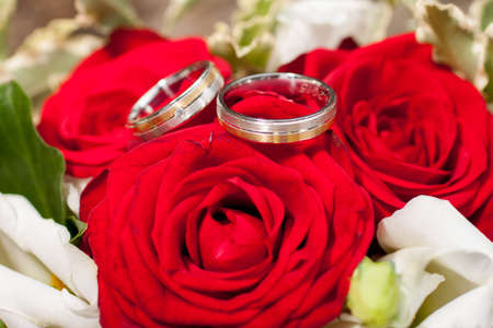Wedding silver golden rings on a bunch of flowers with red roses