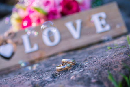 Wedding golden rings on a wooden surface in front of sign with the word love and soap bubbles