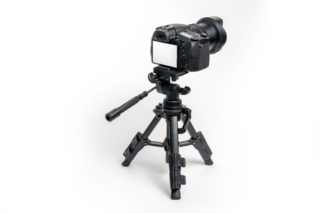 Digital camera and tripod isolated on white background