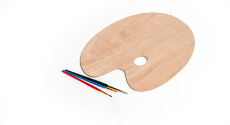 Wooden art palette with paint brush on white isolated 免版税图像