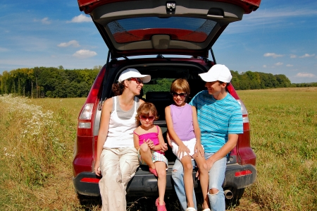 Family of four near their car on vacation photo