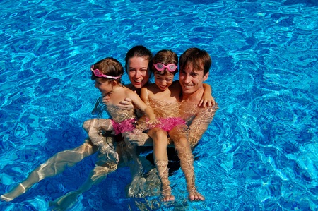 Happy family of four having fun in swimming pool photo