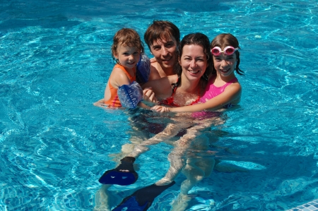Happy family with two kids having fun in swimming pool photo