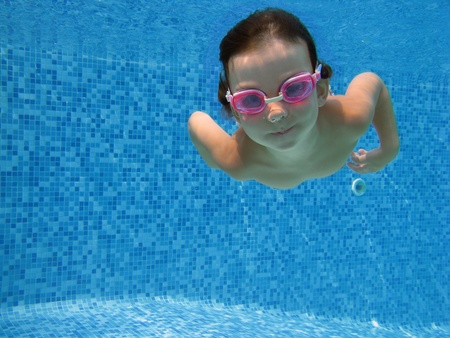 Child swimming underwater in the pool photo