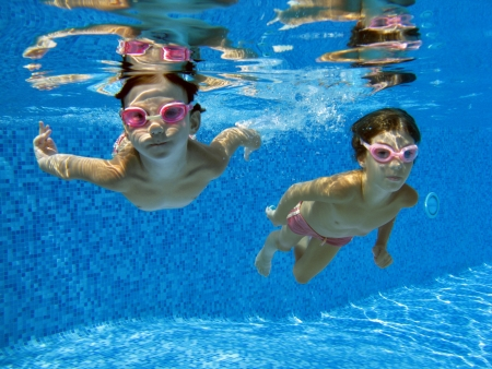under water: Two underwater girls in swimming pool Stock Photo