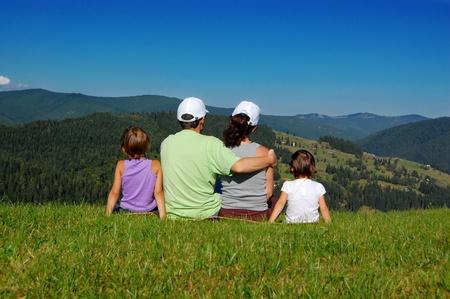 familia viaje: Familia de sus padres y dos ni�os sentados en el c�sped y mirando la hermosa vista de la monta�a Foto de archivo