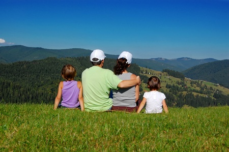 Family of parents and two kids sitting on the grass and looking at the beautiful mountain view photo
