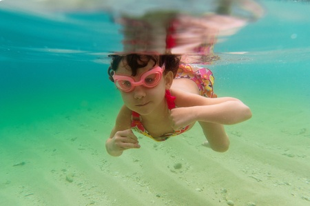 explore: Child swimming underwater in sea