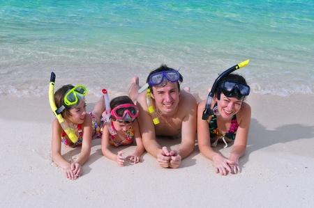 travel family: Familia en snorkels en playa tropical  Foto de archivo