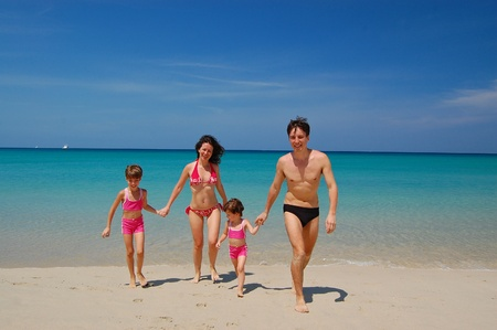swimming suit: Family of four in swimming suits on the beach Stock Photo