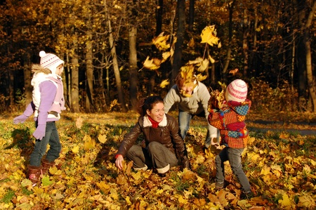 Happy family with two kids throwing leaves in autumn park photo