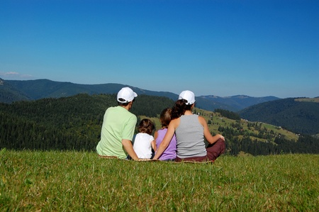 kid sitting: Family of parents and two kids sitting on the grass and looking at the beautiful mountain view