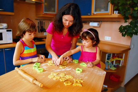 Mother and two daughters baking together photo
