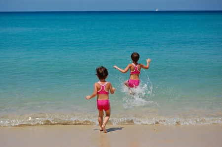 Two little girls running to the sea photo