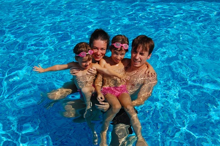 pool preteen: Happy family of four having fun in swimming pool Stock Photo