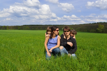 Happy family with two kids on green field Stock Photo - 9454712