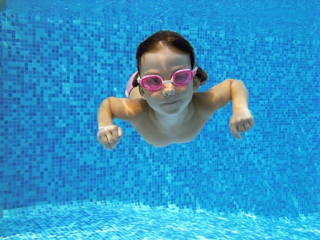swim goggles: Kid swimming underwater in the pool Stock Photo