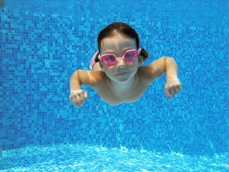 swim goggles: Ni�o nadando bajo el agua en la piscina