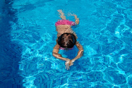 Little child swimming in the pool photo