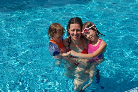 Mother with kids in swimming pool photo