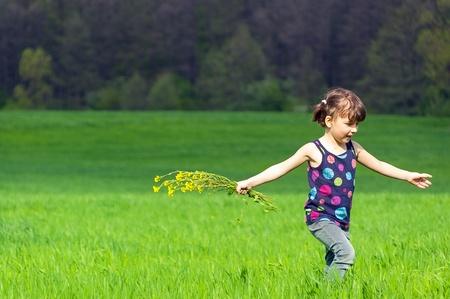Ni�a con flores en campo verde Foto de archivo - 9485320