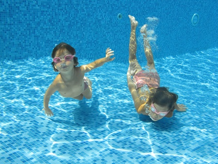 Two underwater kids in swimming pool Stock Photo - 9485325