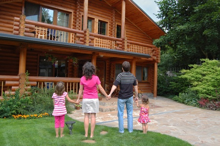 Happy family with two kids near wooden house photo