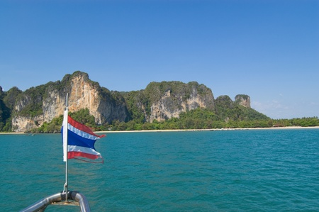 Limestone cliffs in Krabi province and flag of Thailand photo