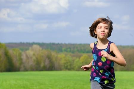 Girl running outdoors on green field