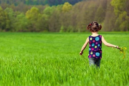 緑の野原の花を持つ少女 写真素材