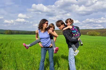 piggyback ride: Happy family outdoors. Parents giving their kids piggyback ride Stock Photo