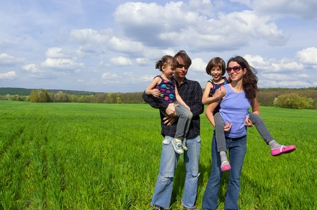 Happy family outdoors. Parents giving their kids piggyback ride photo