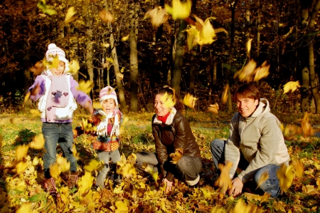 Happy family with two kids throwing leaves in autumn park Stock Photo