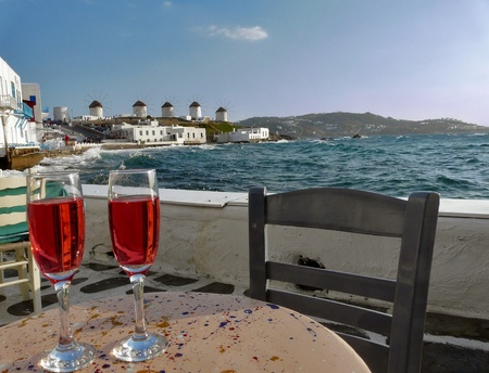 greek island: Two glasses of wine on café table. Mykonos island, Greece