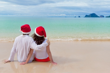 Christmas tropical vacation. Romantic couple in santa hats on beach