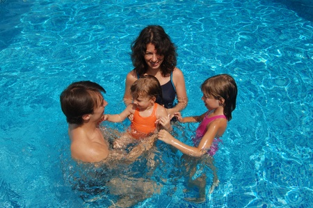 pool preteen: Happy family with two kids having fun in swimming pool Stock Photo