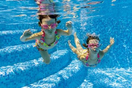 swim goggles: Dos ni�os bajo el agua en la piscina