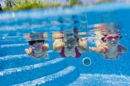 ni�os nadando: Familia bajo el agua en la piscina