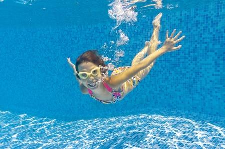 Happy smiling underwater kid in swimming pool photo