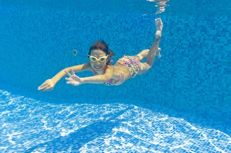 Happy smiling underwater kid in swimming pool Stock Photo - 9759895