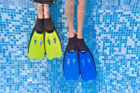Underwater kid's legs in fins in swimming pool