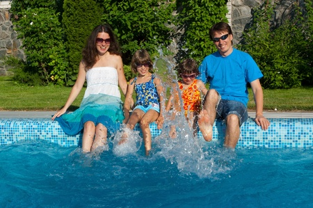 Family vacation. Parents with two kids having fun near swimming pool photo