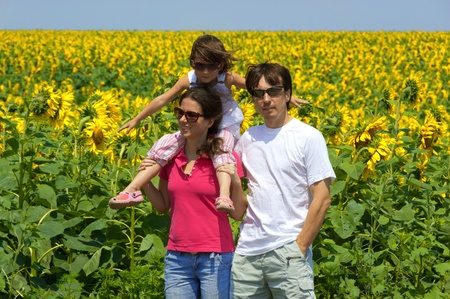 Family vacation. Parents with kid on sunflower field photo